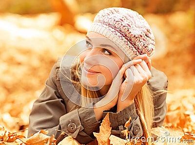 Cute female lay on fall leaves