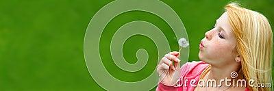 Cute female teenager blowing a dandelion