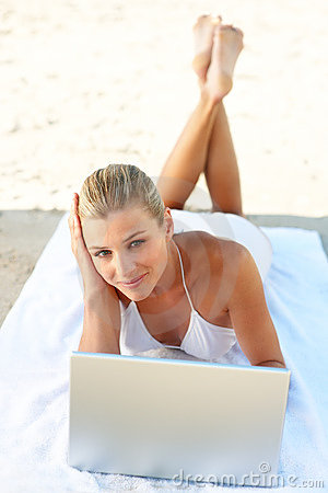 Cute female in white bikini with a laptop