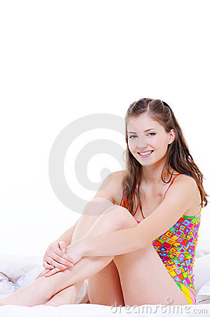 Cute fresh pretty young girl sitting on bed