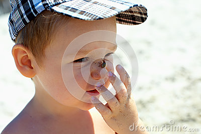 Cute funny baby boy catching bug on nose