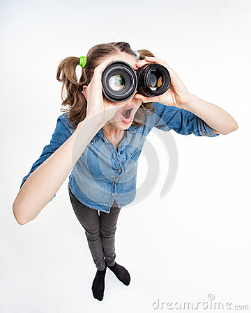 Cute funny girl with two pony tails looking thru photo lenses- wide angle