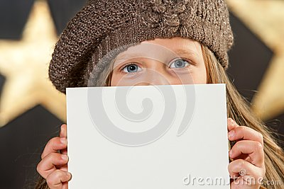 Cute girl with beanie hiding behind white card.