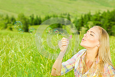 Cute girl blowing bubbles outdoors