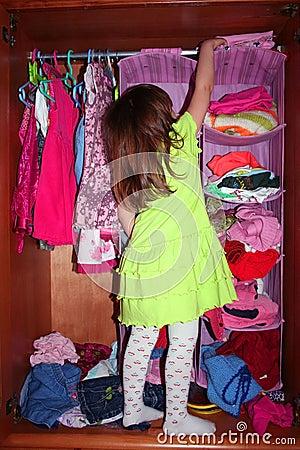 A cute girl choosing dress