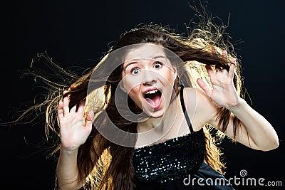 Cute girl with dark long hair shouting on black