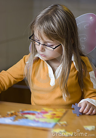 Cute girl doing jigsaw puzzle