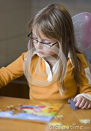 Cute girl doing jigsaw puzzle