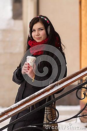 Cute girl in earplugs with coffee cup