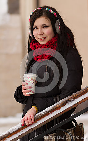 Cute girl in earplugs with coffee cup