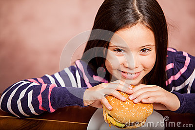 Cute girl enjoying a hamburger