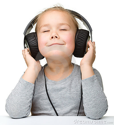 Cute girl enjoying music using headphones