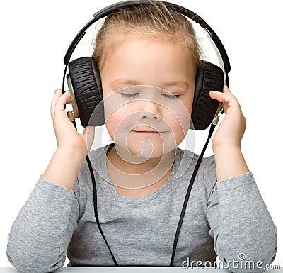 Cute girl enjoying music using headphones