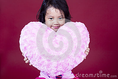 Cute girl with heart on pink background