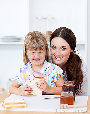 Cute girl and her mother eating slices of bread