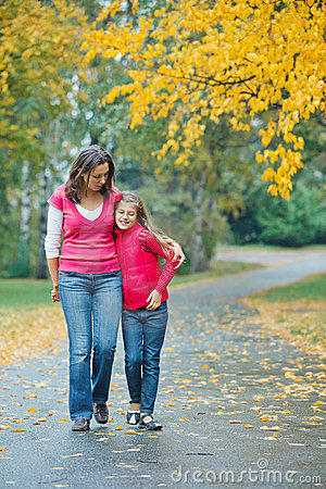 Cute girl with her mother walking in park