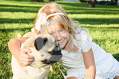 Cute girl hugging with lovely dog at the park