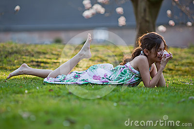 Cute girl lies dreamy in the grass