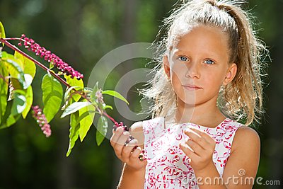 Cute girl outdoors picking berries.