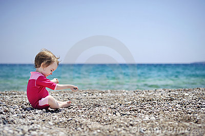 Cute girl playing on pebble beach