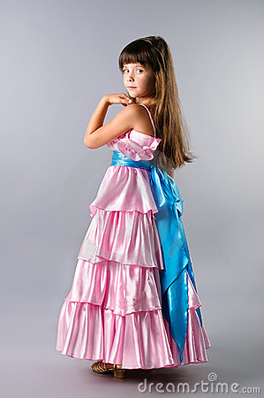 A cute girl posing in a prom pink dress in studio