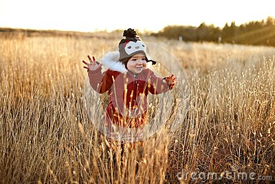 Cute girl running through a field at sunset