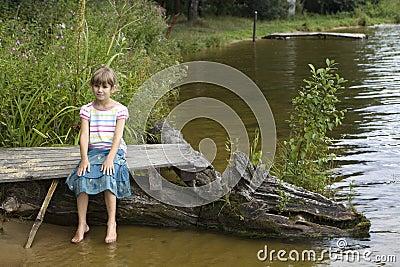 Cute girl sitting on bridge near river