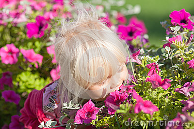 Cute girl smells flowers