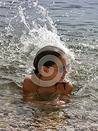 Cute girl splashes in the sea