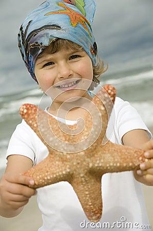 Cute girl with starfish on the beach
