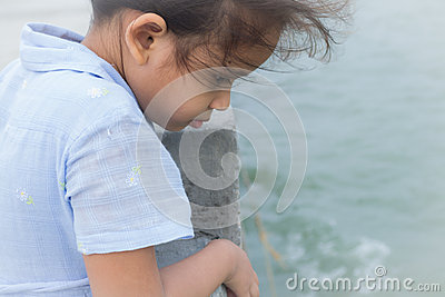 A cute girl is staring to the sea