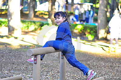 Cute girl try to reach higher plank at playground