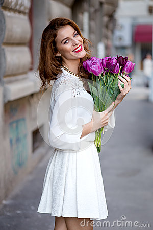 Cute girl in white dress and a beautiful bouquet of tulips. Stock Photo