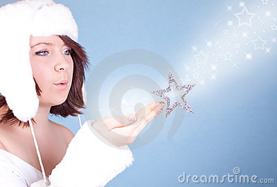 Cute  girl in white hat blowing a snow