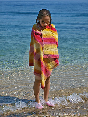 Cute girl wrapped in towel standing in the sea