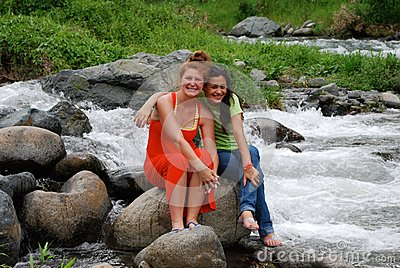 Cute girls sitting by rapids