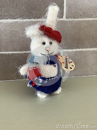 Cute hand made hare or rabbit artist toy knitted with paints and scarf Stock Photo