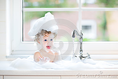 Cute happy baby girl playing with foam in kitchen sink