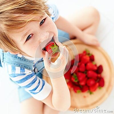 Free Cute Happy Kid Eating Tasty Ripe Strawberries Stock Photo - 92941650