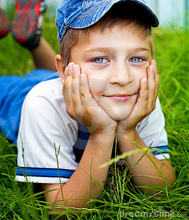 Cute happy kid laying on grass outdoor