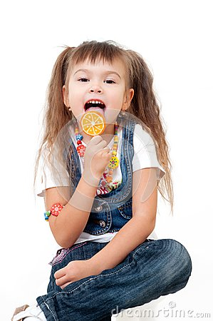 Cute happy little girls tasting brigh lollipop