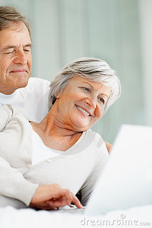 Cute happy senior couple using laptop while in bed