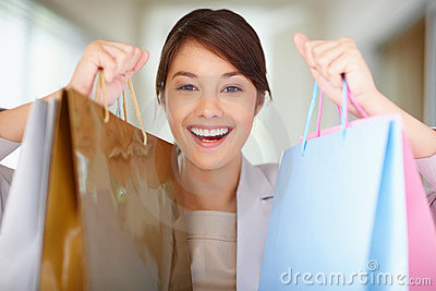 Cute happy woman holding her shopping bags