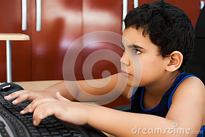 Cute hispanic  boy typing on a computer