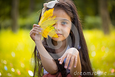 Cute hispanic girl  hiding over yellow leaf