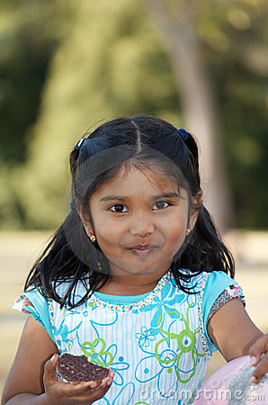 Cute Indian child eating biscuit