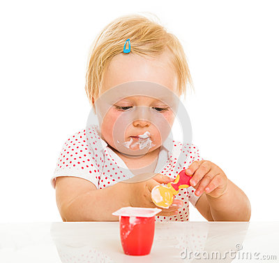 Cute infant girl learining to eat