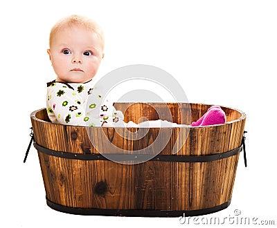 Cute infant in wooden bucket