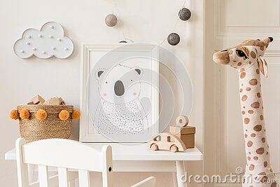 Cute interior of kid room with baby accessories, toys and poster frame. Stock Photo