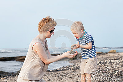 Cute kid at the beach with his mother